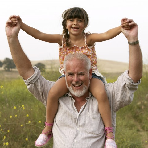 A Grandfather Holding His Granddaughter on His Shoulders