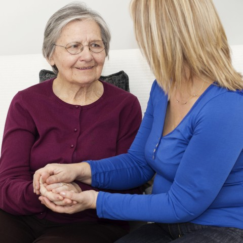 A Woman Sitting Next to an Older Lady and Holding Her Hand