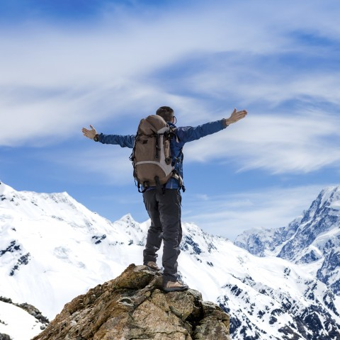 Hiker Standing with Spread Arms on a Mountain