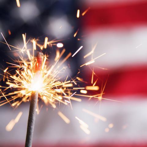 Sparkler in front of U.S. flag