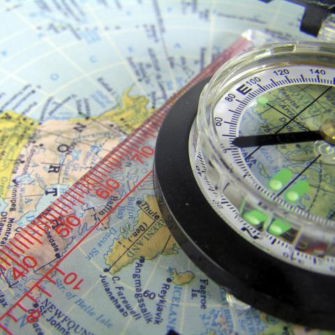 A black compass on a colored map