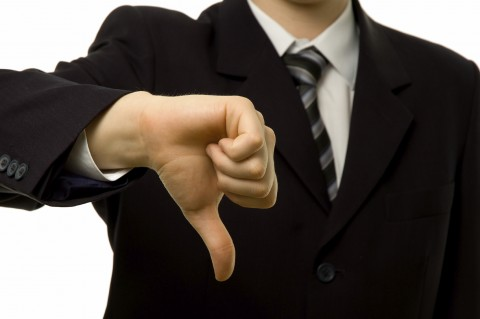 A Man in a Suit Showing Thumbs Down
