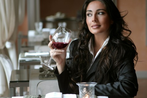 Well-dressed woman drinking red wine in a restaurant