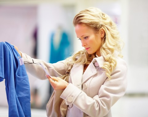 Blonde Woman Staring at a Price Tag of a Blue Dress.