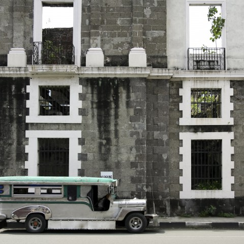 Jeepney taxi parked at the side of a building