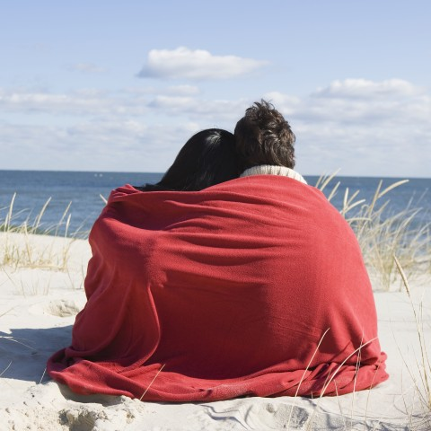 Couple on Beach Wrapped in Blanket