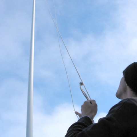 Man Hoisting a Flag