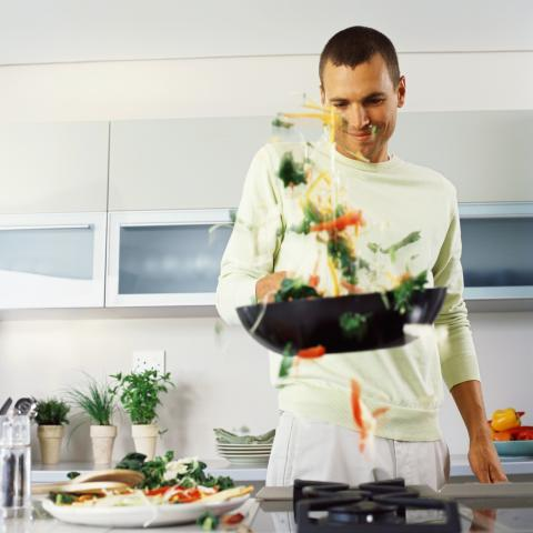 Man in a kitchen, tossing food in a wok