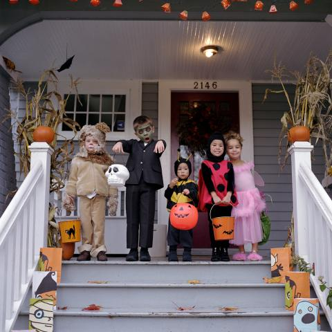 A Group of Children Dressed in Costumes and Trick-or-treating