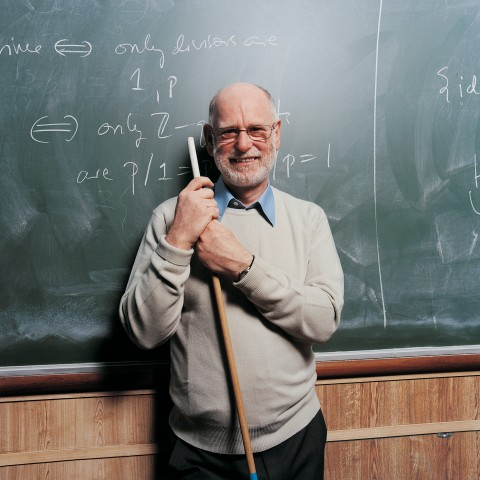 Old Teacher in Front of a Blackboard