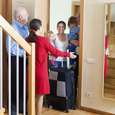 A Couple Meeting Guests with Luggage at Their Front Door.