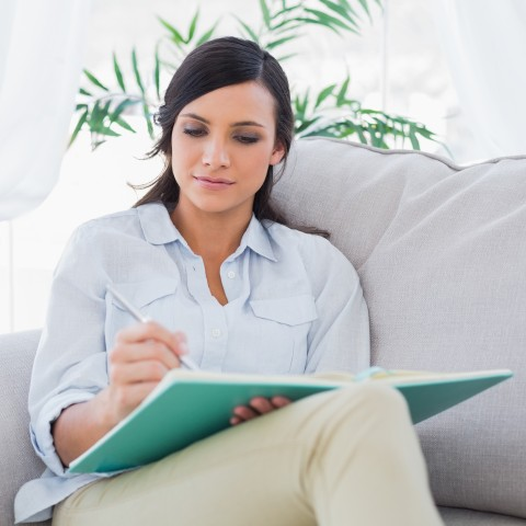 Woman Writing on Couch