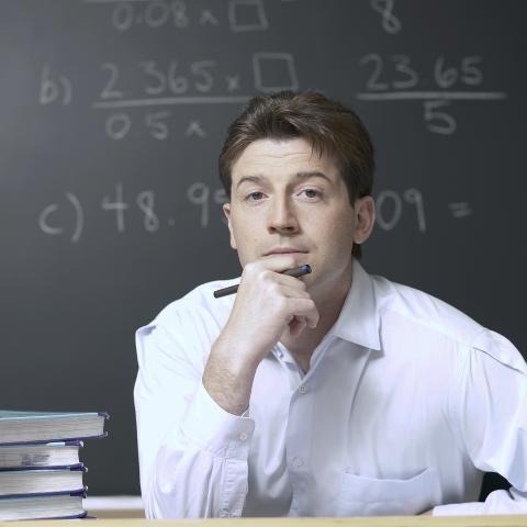 Mathematician Thinking in Front of Black Board with Numbers
