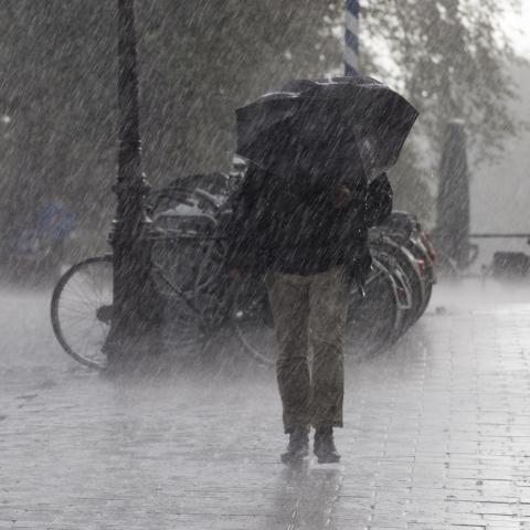 Person Struggling to Walk in Heavy Rain
