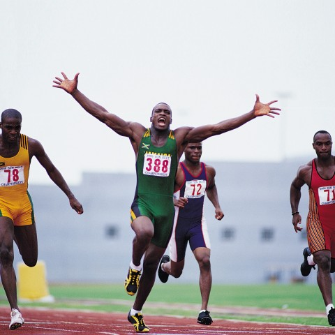 Athlete on Track Shouting in Victory with Arms Raised