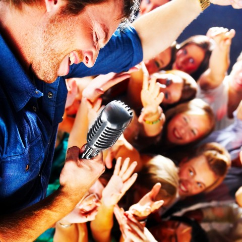 Singer Holding Mic Leaning Over His Swooning Audience