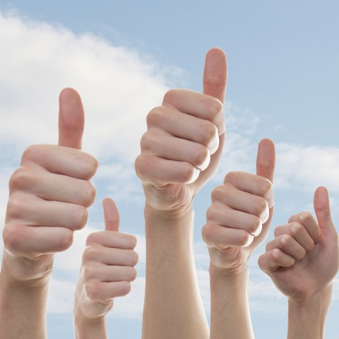 Five hands giving a thumbs up against a cloudy blue sky