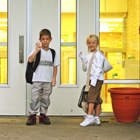 Boy and Girl Standing at a Door Waving Goodbye.