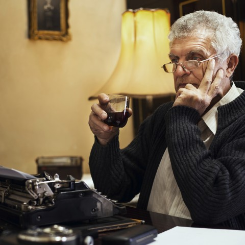 Man Sitting at Typewriter with Drink