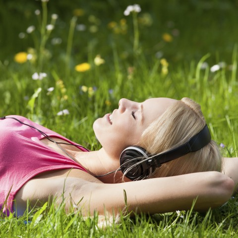 Woman Lying in Grass Listening to Music