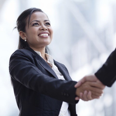 Smiling Woman in a Business Suit Shaking Hands with a Man