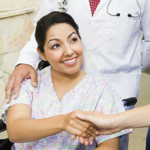 Female Patient in Wheelchair Greeting Someone with a Handshake