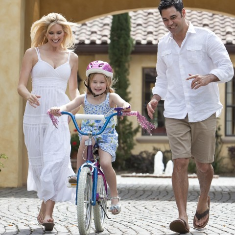 A Couple Helping Their Daughter Ride a Bike