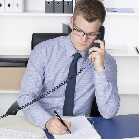 A Young Businessman Taking Notes During a Phone Call