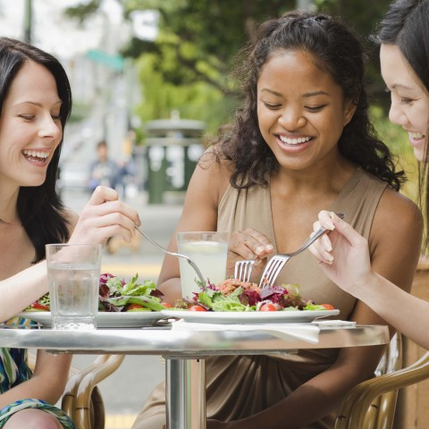 Three Women Sitting at a Table Eating Outside at a Restaurant.