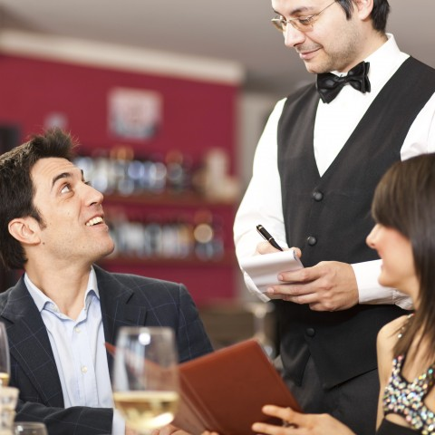 A Man and a Woman at a Restaurant Ordering from a Waiter