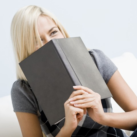 Laughing Young Woman Holding a Book Over Her Mouth.