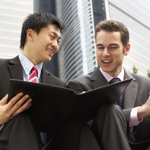 Two Men in a Business Suits Discussing Something in a Folder
