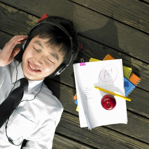A Kid Listening to Music, Happy about an A+ on His Homework