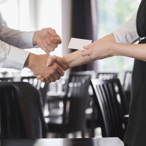A Man and Woman's Arms and Hands in a Handshake, While Exchanging Business Cards