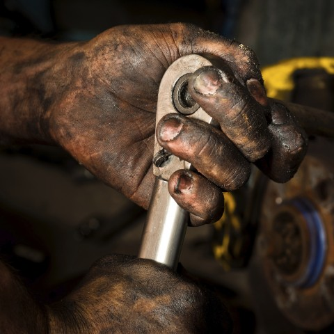 Greasy Mechanic's Hand Holding a Tool