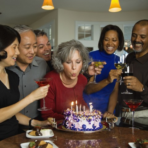 Older Woman Blowing Out Candles on a Birthday Cake Surrounded by Friends.
