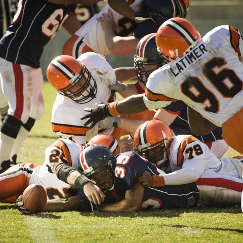 Football Players Tackling Each Other