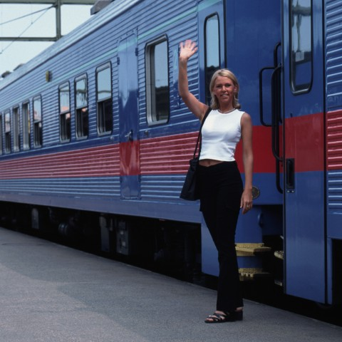 Pretty Blonde Girl Waving Goodbye Next to a Blue Train