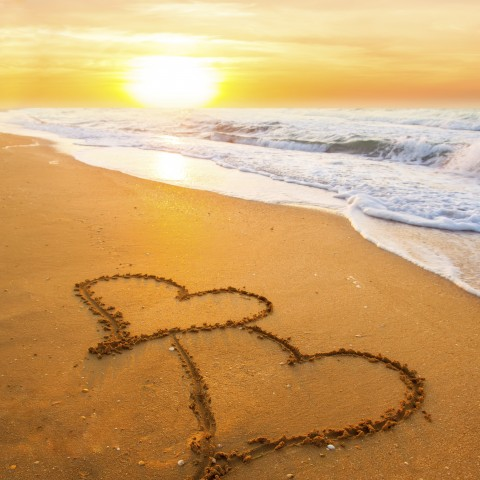 Two Hearts Drawn in the Sand on the Beach at Sunset.