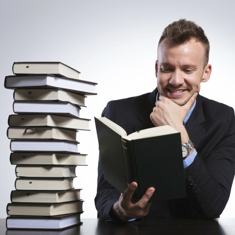Man Reading Lots of Books