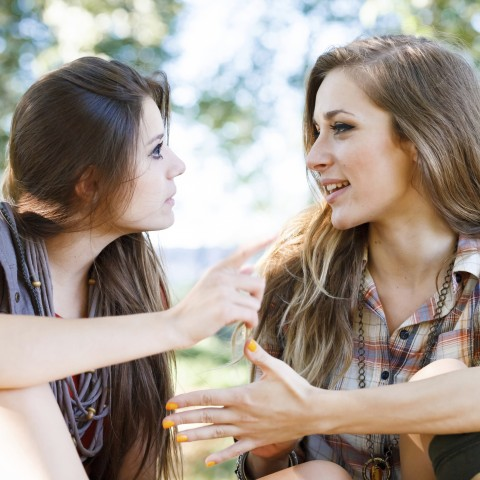 Two Young Women Chatting Animatedly.