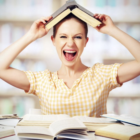 A Woman Laughing with a Book on Her Head