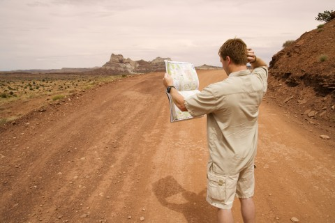 Man lost on a dusty road, looking at a road map and scratching his head