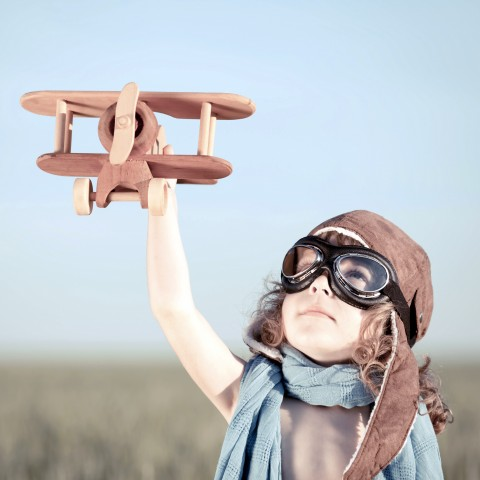 BOY HOLDING A TOY AIRPLANE