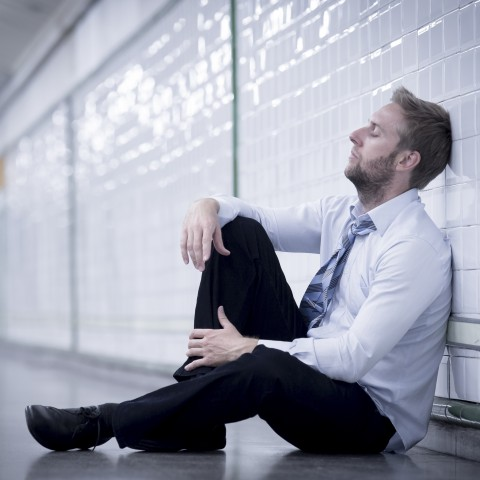Dejected, sad Young Man Sitting on the Floor in a Station