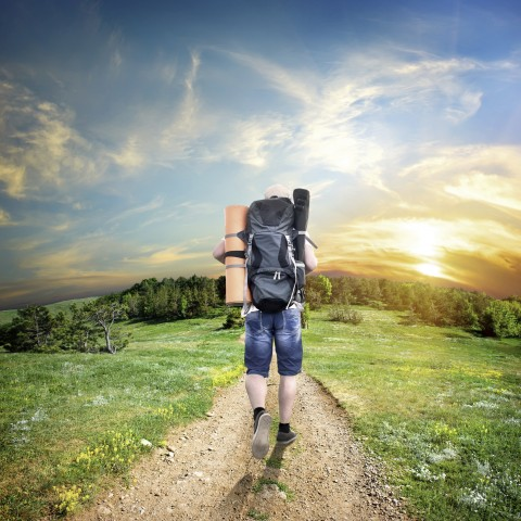 A Person with a Backpack Walking on a Path in Nature Towards Sunset