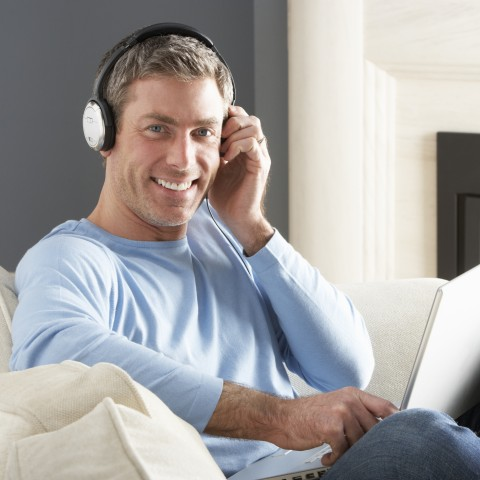Smiling Young Guy with Blue Sweater, Sitting with Headphones On