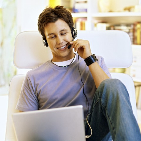 Young Smiling Male Student Learning Language in Front of Laptop with Earphones
