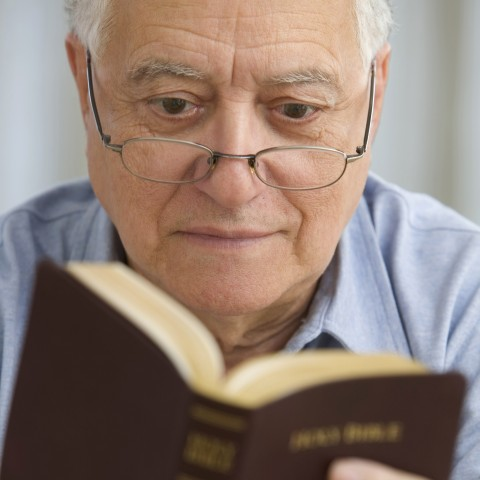 An Old Man with Glasses Reading the Bible
