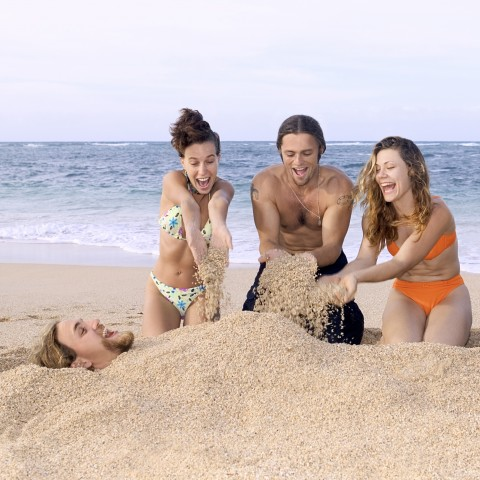 Four Adults Playing on the Beach in the Sand